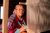 istock Elderly Native American Navajo Woman Weaving a Traditional Tribal Blanket on a loom inside a Hogan 1069425422