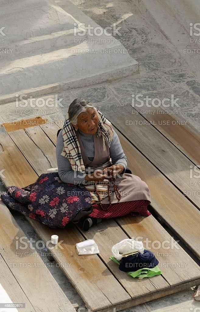 Elderly Nepalese woman prays royalty-free stock photo