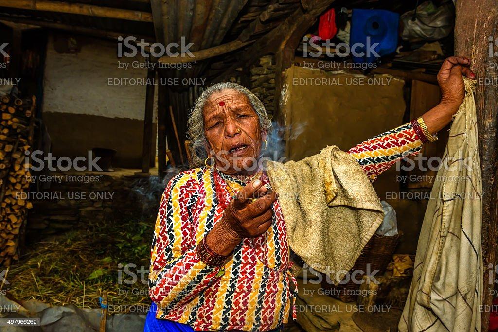 Elderly nepalese woman smoking a cigarette while talking stock photo