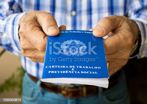 istock Elderly old male hands worker holding portfolio work permit of Ministry of Labor and Social Security of Brazil(Translation: