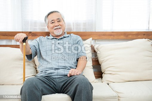 elderly old senior man sitting, resting his hands on wooden walking stick sitting on couch in living room in house after retirement.