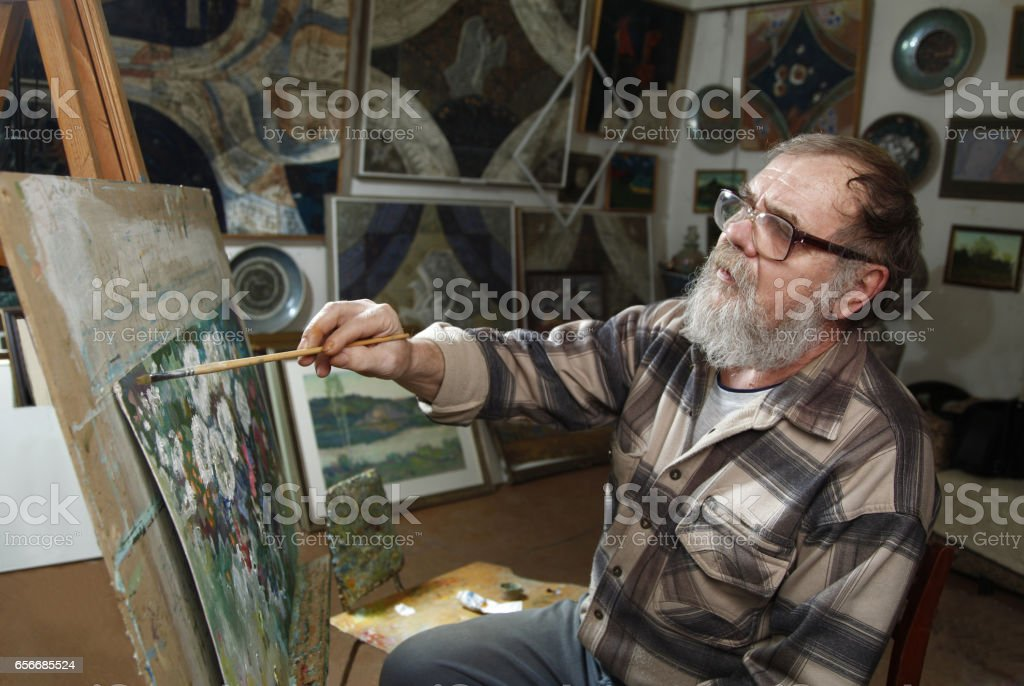 Elderly painter with beard and glasses draws a flowers picture by oil paint in art workshop stock photo