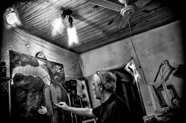 Elderly painter working in his atelier. - foto de acervo