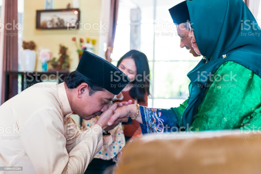 Elderly parents giving blessings to their son's family during Hari Raya Aidilfitri stock photo