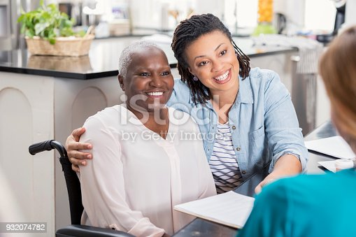 932074776istockphoto Elderly patient and her daughter talk with home healthcare nurse 932074782