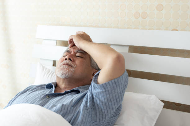 Elderly patients in bed, Asian senior man patients headache hands on forehead - medical and healthcare concept stock photo