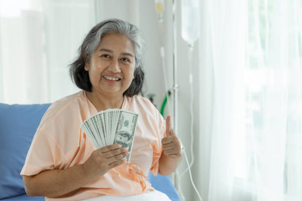 elderly patients injury  woman on Patient's bed in hospital  holding us dollar bills feel happy from getting insurance money From insurance companies stock photo