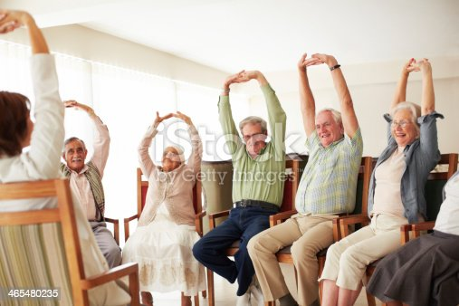 istock Elderly people in chairs stretch arms 465480235