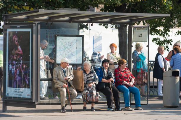 Os povos idosos sentam-se em uma parada de transporte público - foto de acervo