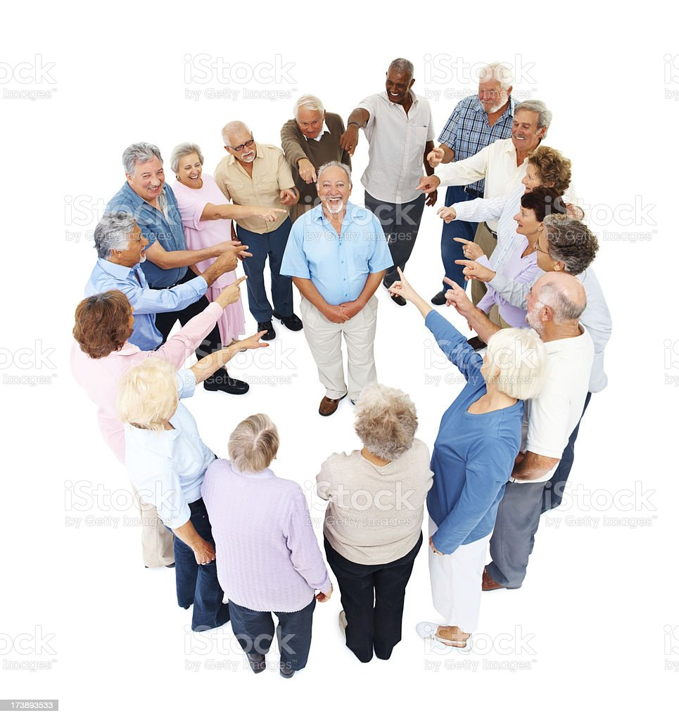 Elderly people standing in circle pointing at man royalty-free stock photo