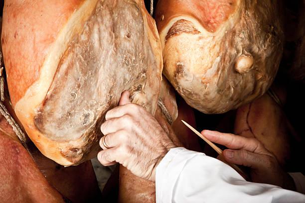 Elderly person handling Parma ham stock photo