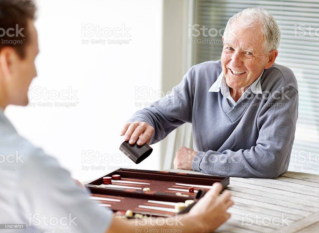 Elderly person playing backgammon with a young guy stock photo