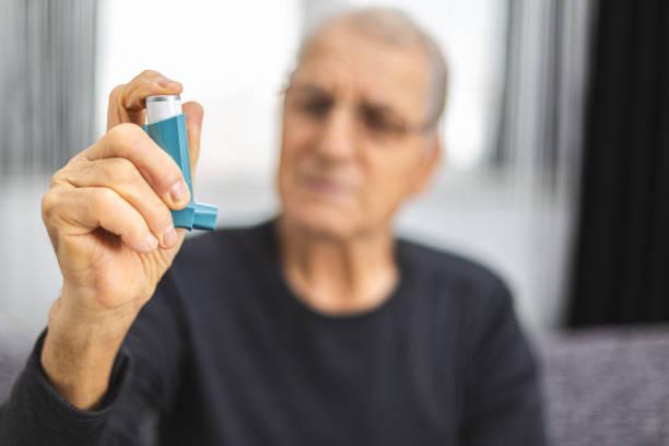 Elderly person using an asthma spray. Senior man ready for using an asthma inhaler stock photo