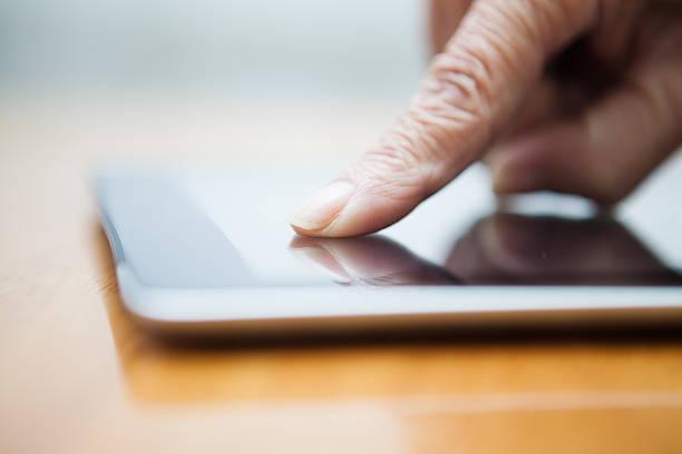 Älterer finger zeigt auf tablet PC – Foto