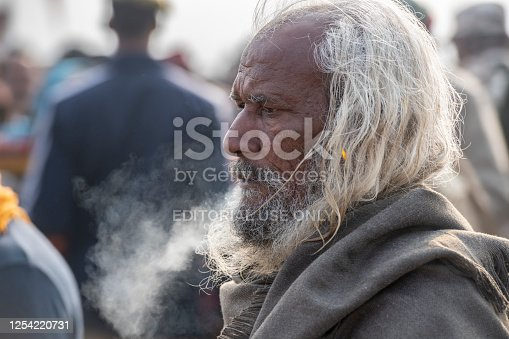 Elderly pilgrim, with white long hair and beard, breathing, early morning. Photo taken during Kumbh Mela 2019 in Prayagraj (Allahabad), India. Mornings can be cold (under 12º Celcius) and misty in the city, during winter Kumbh Mela celebrations. Kumbh Mela or Kumbha Mela is a major pilgrimage and festival in Hinduism, and probably the greatest religious festival in the World. It is celebrated in a cycle of approximately 12 years at four river-bank pilgrimage sites: the Allahabad (Ganges-Yamuna Sarasvati rivers confluence), Haridwar (Ganges), Nashik (Godavari), and Ujjain (Shipra). The festival is marked by a ritual dip in the waters, but it is also a celebration of community commerce with numerous fairs, education, religious discourses by saints, mass feedings of monks or the poor, and entertainment spectacles. Pilgrims believe that bathing in these rivers is a means to cleanse them of their sins and favour a better next incarnation.