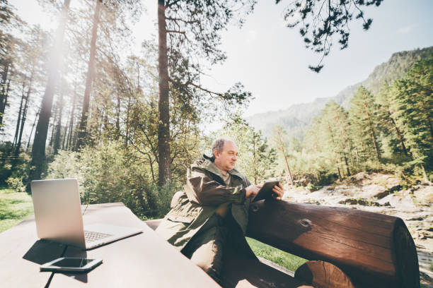 Elderly plus size man in forest with digital pad Mature forest warden is sitting on huge wooden bench with his gadgets and sending report using digital tablet; aged man in camping suit is having work session during his vocations in Altai mountains park ranger stock pictures, royalty-free photos & images