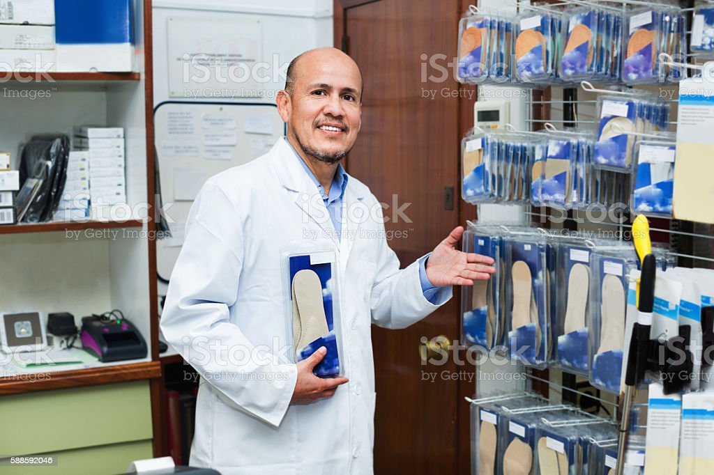 Elderly professional consultant offering orthopaedic insoles stock photo