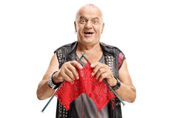 elderly punker knitting and smiling - lavorare a maglia foto e immagini stock