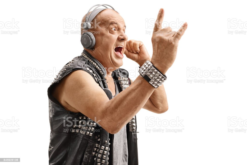 Elderly punker listening to music and making rock hand gesture stock photo