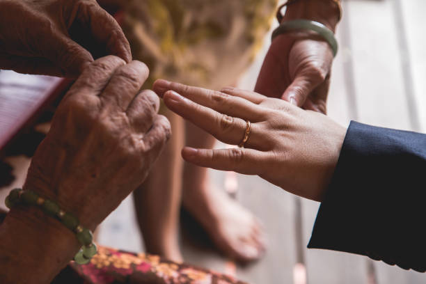 Elderly putting on a gift ring on the newlywed stock photo
