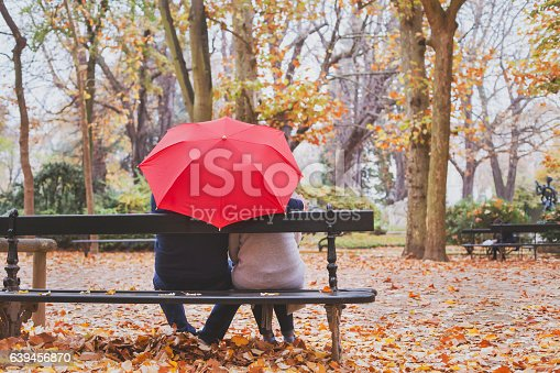istock elderly retired couple sitting together under umbrella 639456870