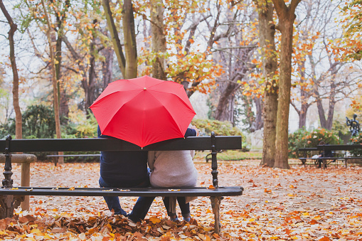elderly retired couple sitting together under umbrella