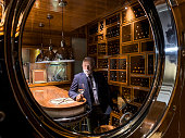 Elegant senior man seen tasting wine through the porthole on a wine cellar on a luxurious yacht.