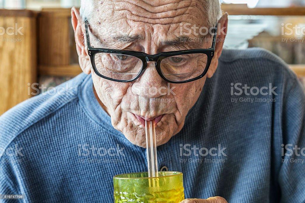 Elderly Senior Adult Man Drinking Water Through Two Straws stock photo