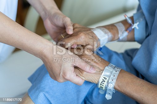 958891774istockphoto Elderly senior aged patient on bed with geriatric doctor holding hands for trust and nursing health care, medical treatment, caregiver and in-patient ward healthcare in hospital 1189617170