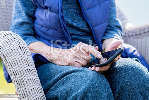 Senior Caucasian Woman's Hands Using the Touch Screen on a Smart Phone Outdoors