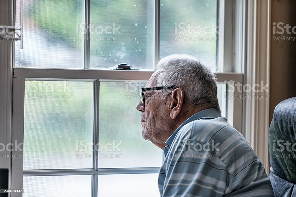 Elderly Senior Dementia Man Looking Through Grungy Window stock photo