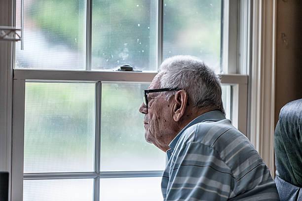 idosos sénior demência homem olhando através da janela de grunge - old men window imagens e fotografias de stock