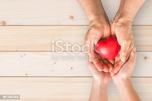 istock Elderly senior person or grandparent's hands with red heart  in support of nursing family caregiver for national hospice palliative care and family caregivers month concept 987982650