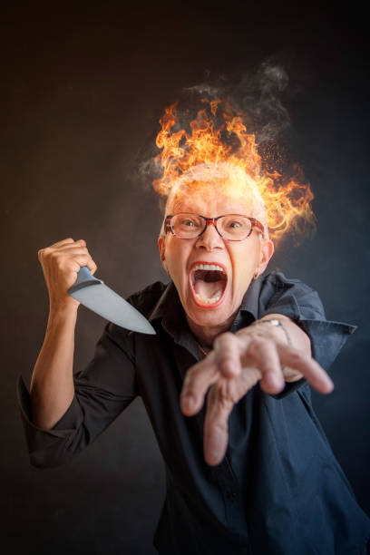 Elderly senior woman about to murder someone with her knige Infuriated angry senior woman slaying, holding a kitchen knife, about to kill someone, her head is on fire cutthroat stock pictures, royalty-free photos & images