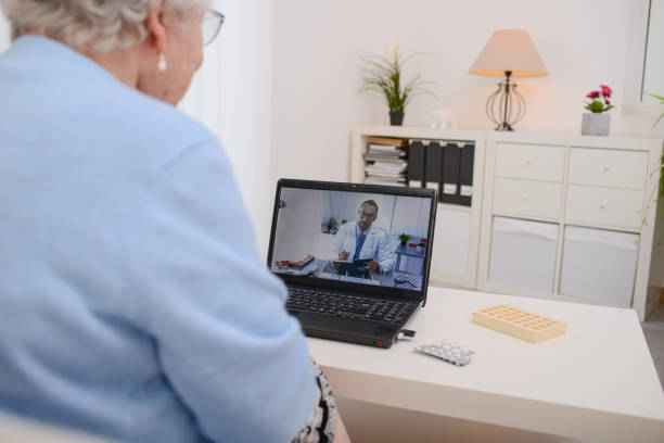 elderly senior woman, having a remote medical consultation with her doctor over internet computer telemedecine diagnostic - telemedicine stock pictures, royalty-free photos & images
