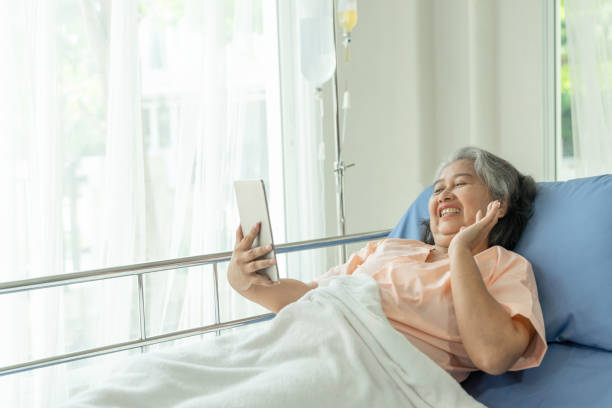 Elderly senior woman patients in hospital bed patients using smart phone call to descendant relatives feel happiness - senior female medical and healthcare concept stock photo