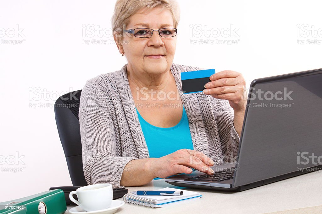 Elderly senior woman with credit card and laptop stock photo