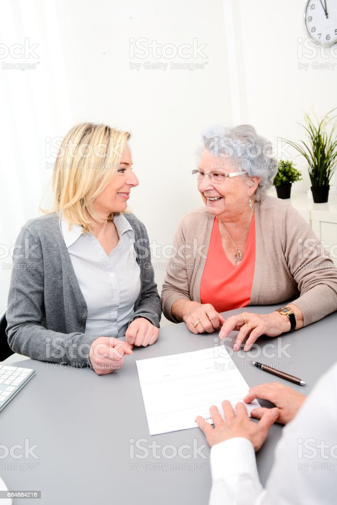 elderly senior woman with daughter signature legacy heritage testament document in a lawyer notary office stock photo