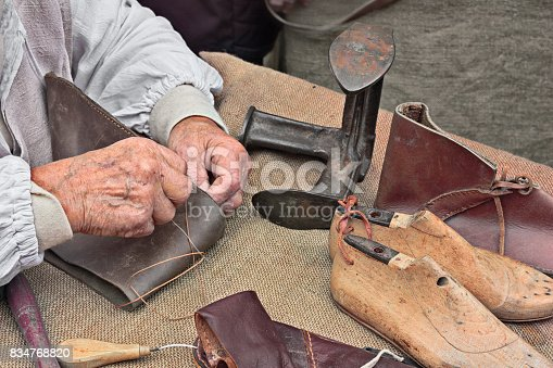 elderly shoemaker makes artisan shoes on an old bench with old tools for leather working