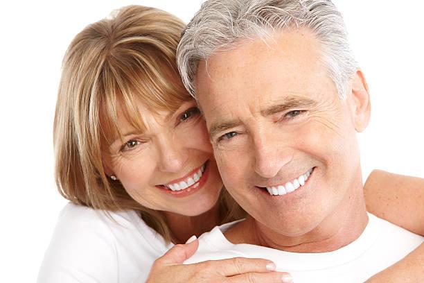 Elderly smiling couple on white background stock photo