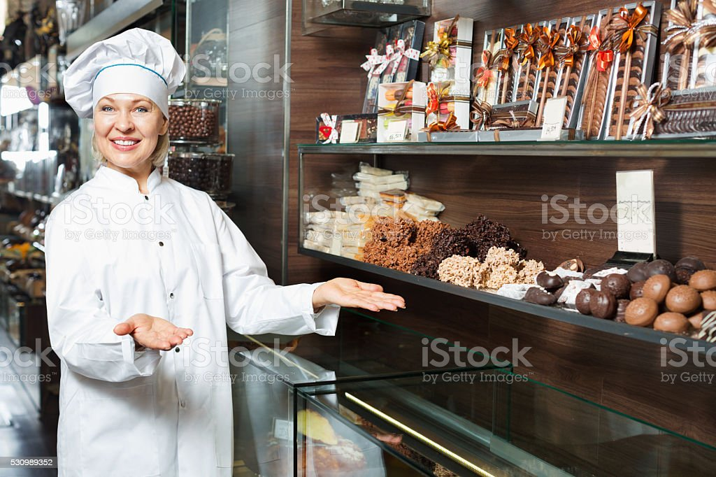 Elderly  smiling seller with dark and white chocolates confectio stock photo