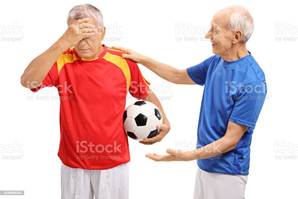 Elderly soccer player consoling another player stock photo