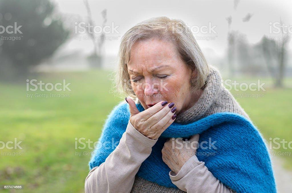 Elderly stylish woman coughing or sneezing stock photo