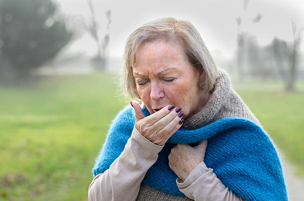 Elderly stylish woman coughing or sneezing bildbanksfoto
