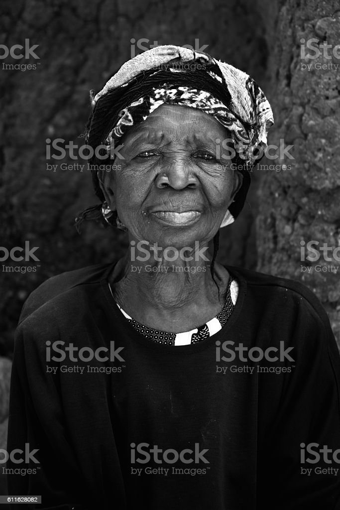 Elderly Togolese woman with head wrapped in scarf stock photo
