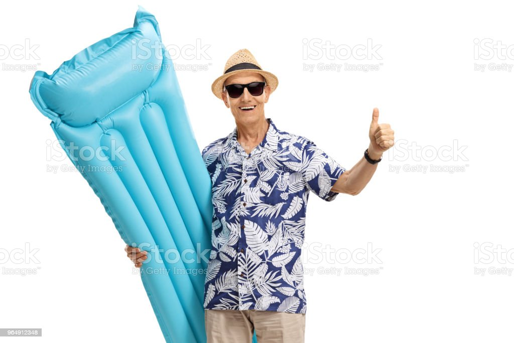 Elderly tourist holding an air mattress and making a thumb up gesture royalty-free stock photo