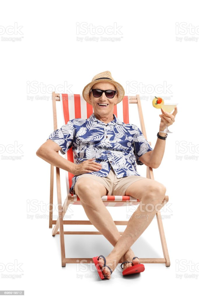 Elderly tourist with a cocktail sitting in a sun lounger stock photo