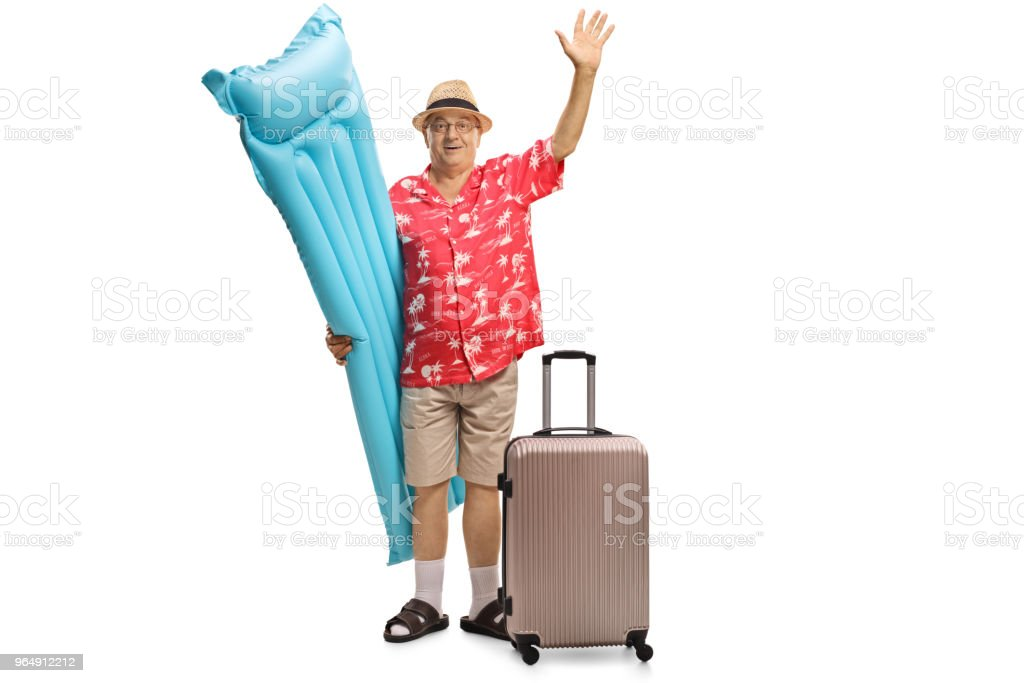 Elderly tourist with an air mattress and a suitcase waving at the camera royalty-free stock photo