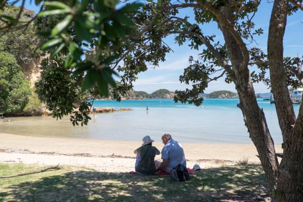 Elderly tourists by the beach on Urupukapuka Island, Bay Of Islands, New Zealand, NZ. stock photo