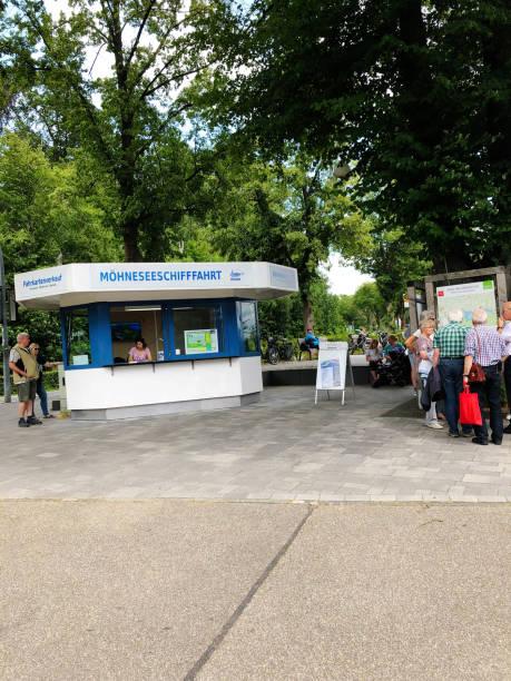 ältere touristen warten auf die fähre auf der möhne-stauseebrücke oder dem möhne-stausee in deutschland. der stausee ist ein künstlicher see in nordrhein-westfalen bei dortmund. der see wird durch die stauung der flüsse möhne und heve gebildet. - nrw ticket stock-fotos und bilder